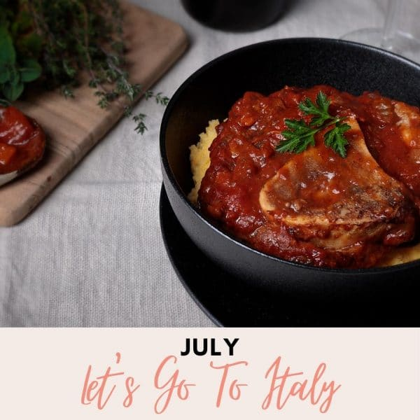 Black bowl with Osso Bucco and a chopping board I the background for Foodie Shots Cooking Experience Let's Go To Italy