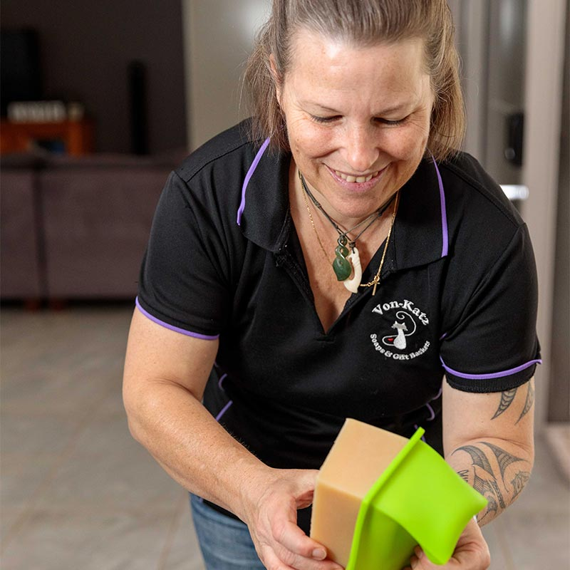 Lady wearing dark shirt with Von Katz logo, pulling soap out of tray