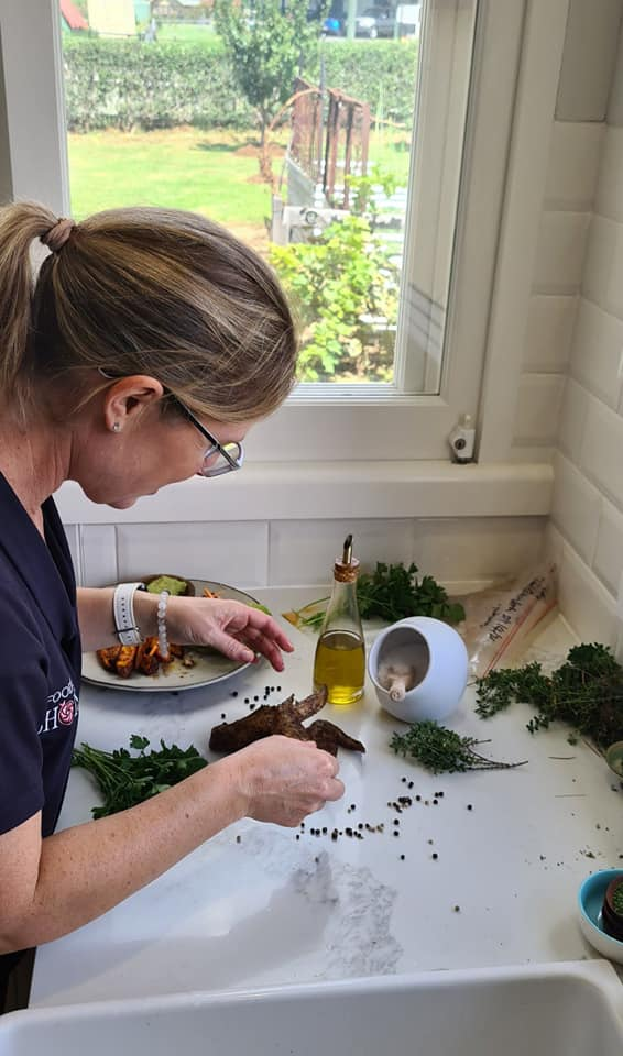 Kat stands over a white kitchen bench arranging props for a photo shoot. On the bench in front of her is a white salt pig, scattered peppercorns, herbs.