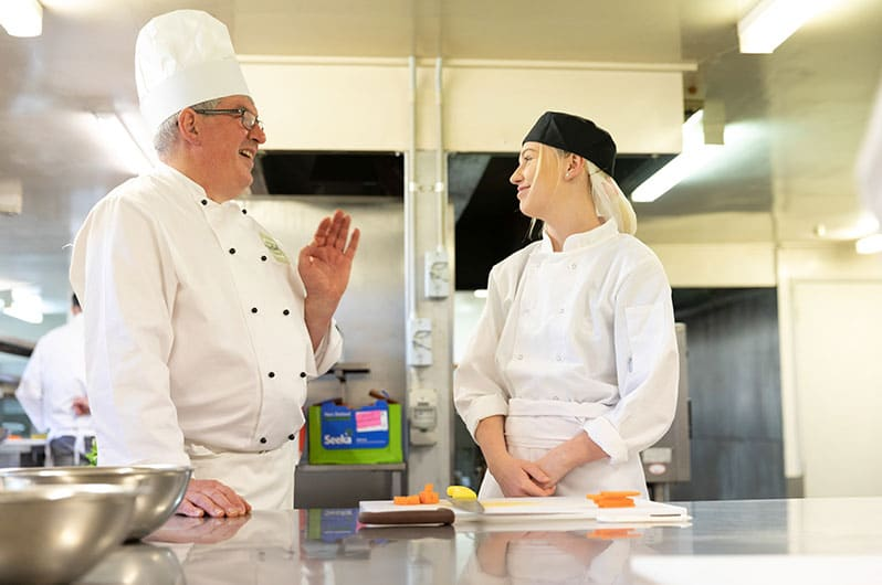 Downs Hospitality and Training Chef Stephen Simon with a trainee in the kitchen