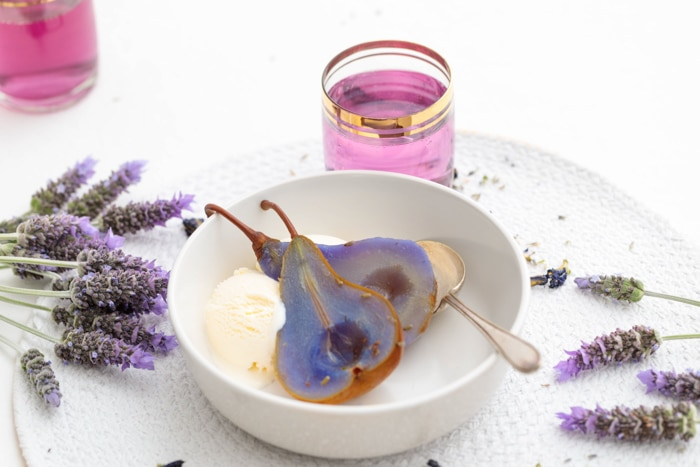 A bowl sits on a white background scattered with sprigs of lavender. In the bowl is a halved poached pear with a vibrant purlpe-blue tone, and a scoop of vanilla icecream, as well as a gold spoon. Behind the bowl is a gold-rimmed glass filled with a vibrant purple liquid