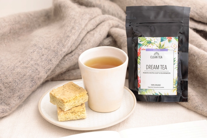 A cup of tea sits on a saucer on a white bench. On the same saucer is a stack of specked shortbread. Next to the tea in a packet of Clean Tea's Cream tea. All these items are sitting on a soft latte-coloured blanket as if perched on a bed