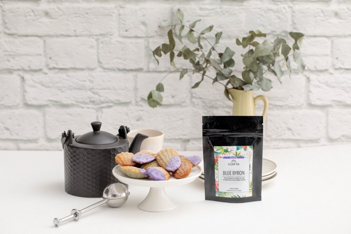 A black packet of Clean Tea's Bue Byron tea sits in front of a yellow vase filled with Austrlaian native branches, on a while bench against a rendered white brick wall. Next to the tea is a dainty white cake stand piled high with madeleines dipped in a lavender-coloured icing. Behind the cake stand is a black teapot and white tea cup, while in front is a silver tea strainer