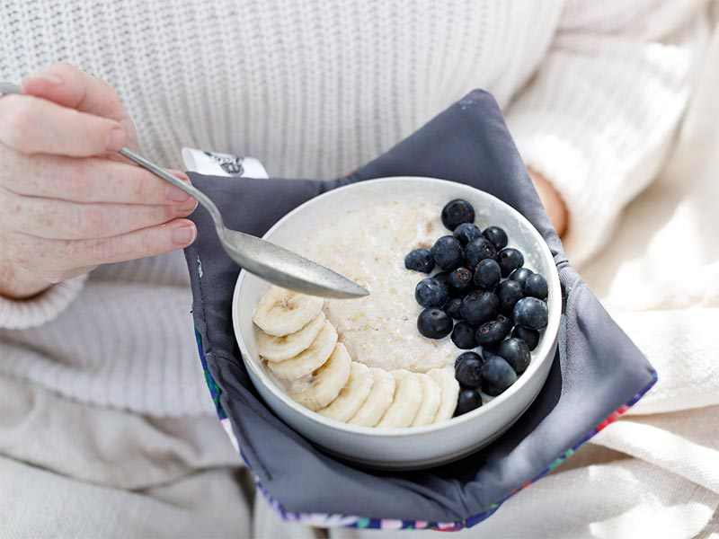 Foodie shots of A bowl of oats, topped with blueberry and bananas is being held in one hand. In the other hand is a spoon angled ready to eat the oats. The bowl has a periwinke blue cosy around it and the backgroud in a cabled white wool