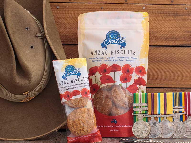 A traditonal Australian Army slouch hat sits on a wooden background with an individual serve pack of Anzac biscuits resting on the edge of the hat. on the other side of the individual pack is a bulk pack of Anzac biscuits with Australian military medals resting on the opposite side