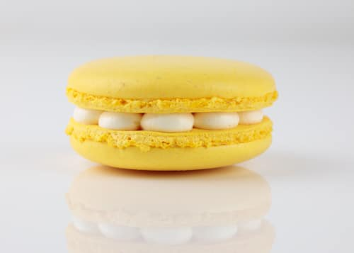 A yellow macaron sits on a white bench, fills with white buttercream
